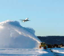 A snowplough clears snow from the runway.