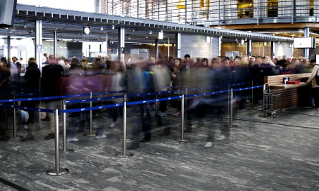 Passengers queuing to pass through airport security.