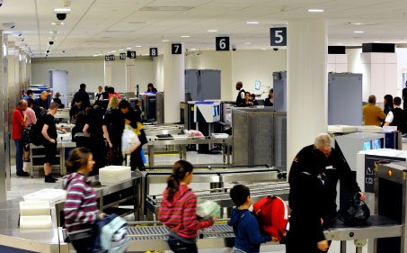 Passengers having their baggage scanned at the airport.